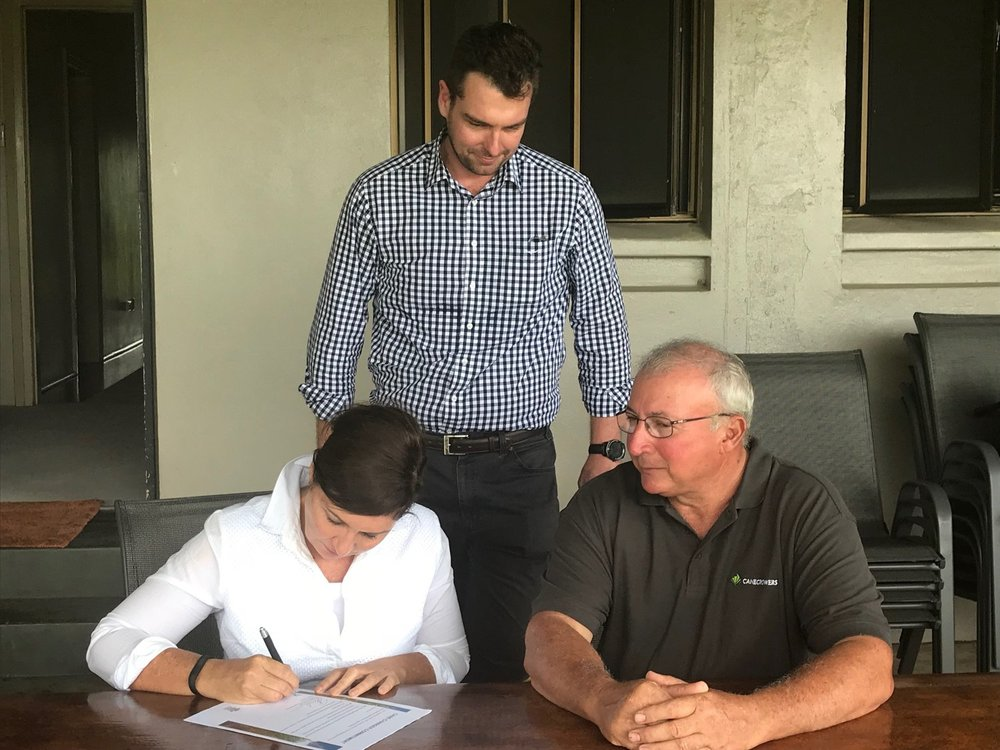 Minister for Environment and the Great Barrier Reef, Minister for Science and Minister for the Arts, Leeanne Enoch, signing a 'Cane Changer Commitment' on CANEGROWERS Innisfail Chairman, Joseph Marano's farm (Right).