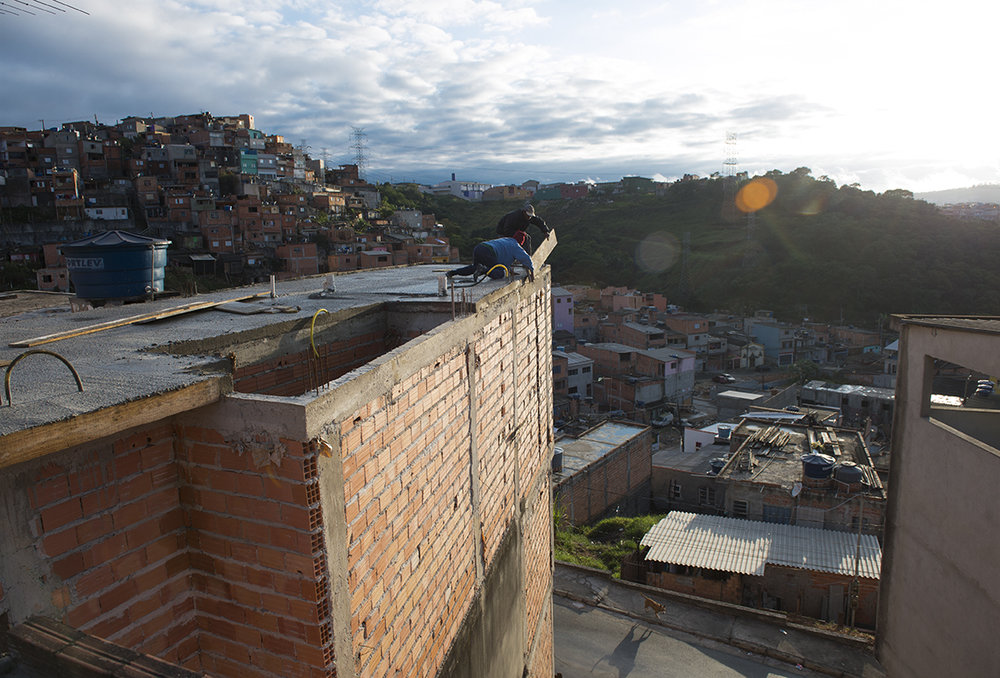 Valdinei Cruz and his assistant bricklayer try to detouch a wood board off the side wall in Santo André favela, São Paulo, August 10, 2016.