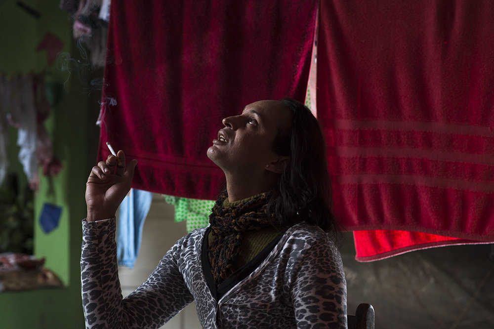 Luciano poses for the camera as he smokes cigarette at a laundry hanging spot outside home in Santo André favela, São Paulo, on August 12, 2016.