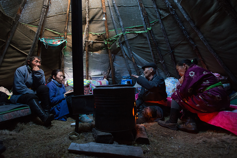 Ganbat (57), an elder of the Tsaatan community in East Taiga, second right, and his wife, Khurlee (58), right, discuss with tour guides, Lkhagvasuren (59), left, and Khaliun Bayartsogt (29), second from left, inside Ganbat's ortz.