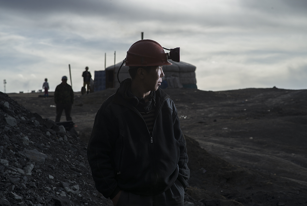 Baasanbat Sainnyambuu, a 35-year old former herder, poses at dusk at the former state-owned Nalaikh coal mine, south of Ulaanbaatar, Mongolia, on April 14, 2016.