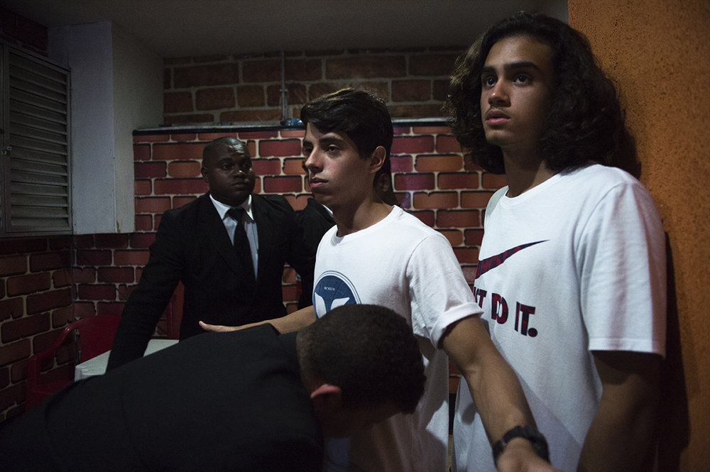 Teens get checked by bouncers at entry at a Baile funk party venue in Rio das Pedras, Rio, on August 19, 2016.