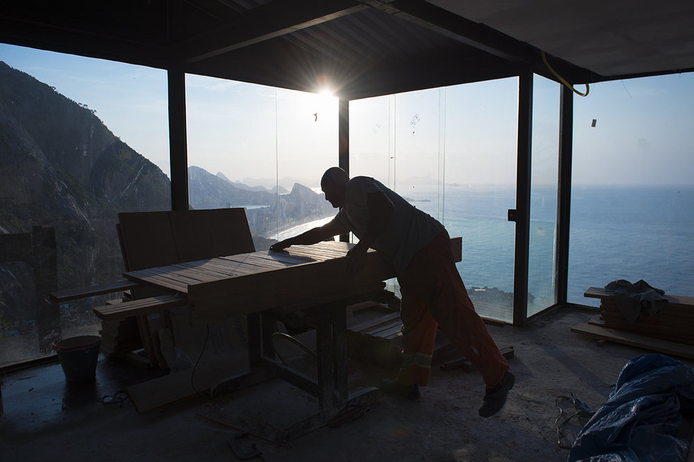 In the early morning bricklayer Gilberto de Oliveira works inside a fancy cafe construction site atop Vidigal favela, overlooking Leblon and Ipanema beaches in Rio de Janeiro on August 19, 2016.
