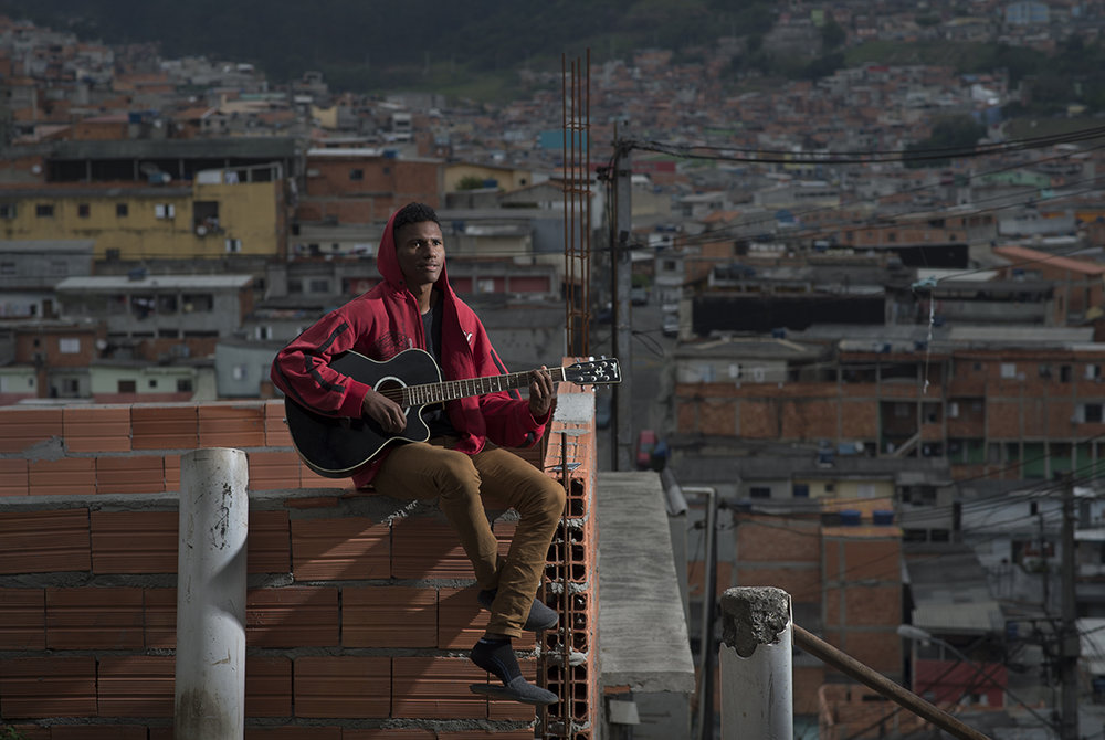 "Matheus Gadelha, a 19-year old unemployed resident of Santo Andre favela, Sao Paulo, Brazil, poses for the camera as he practices a guitar by his home, on August 12, 2016. Matheus dreams to become a professional musician. The teen has never met his father and says ""I'm very happy without him, my mother is everything to me."""