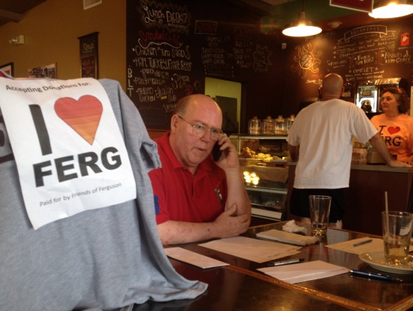 "Brian Fletcher, who loves Ferguson, where he once served as mayor, sits in a coffee shop in August collecting donations for a group he named ""I ❤ Ferguson."""