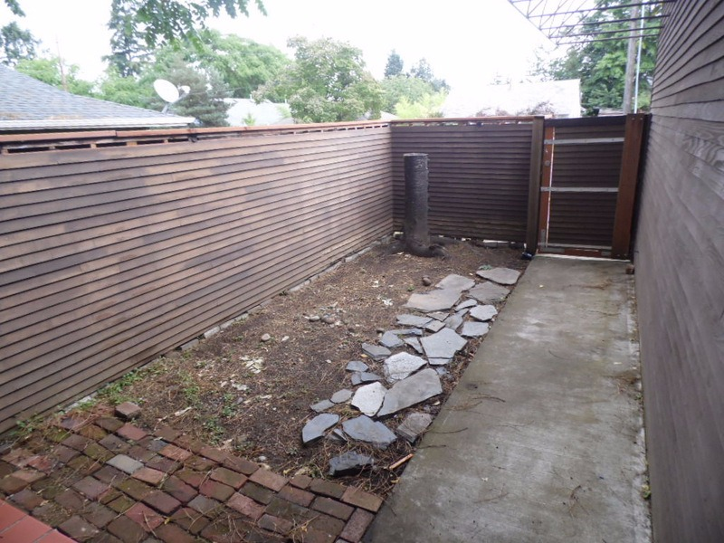 This property has a unique courtyard entry space that needs some attention. A modern upgrade of corrugated metal in this space with a patio deck and planting beds are planned.