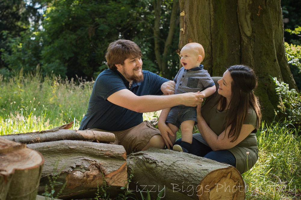 Family photoshoot playing on tree trunks in woods