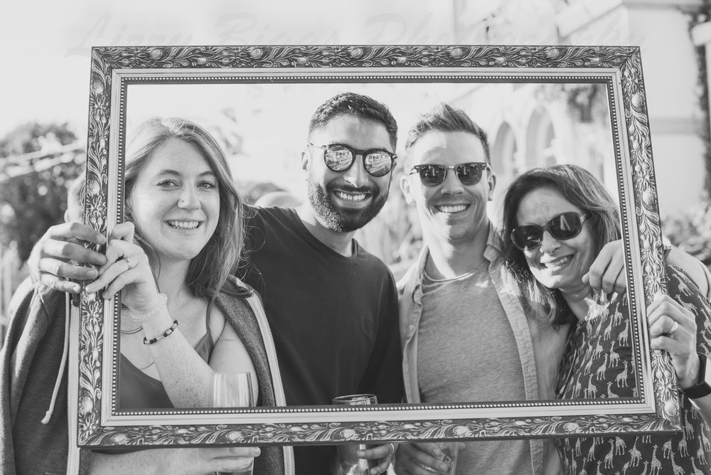 Four people in a picture frame smiling in sunglasses