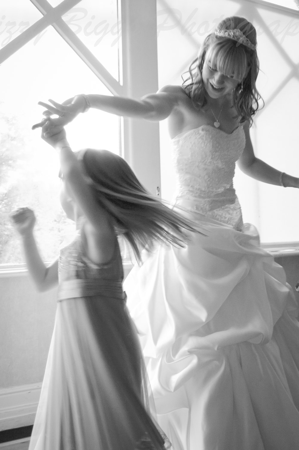 Bride twirling bridesmaid on dance floor backlit in window