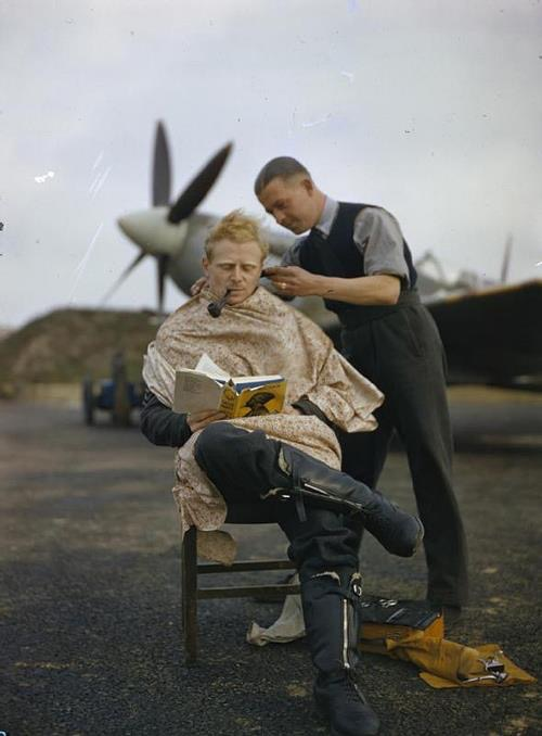 An RAF pilot at Fairlop airfield in Essex has a haircut during a break between sweeps. A Supermarine Spitfire is in the background. 1942.