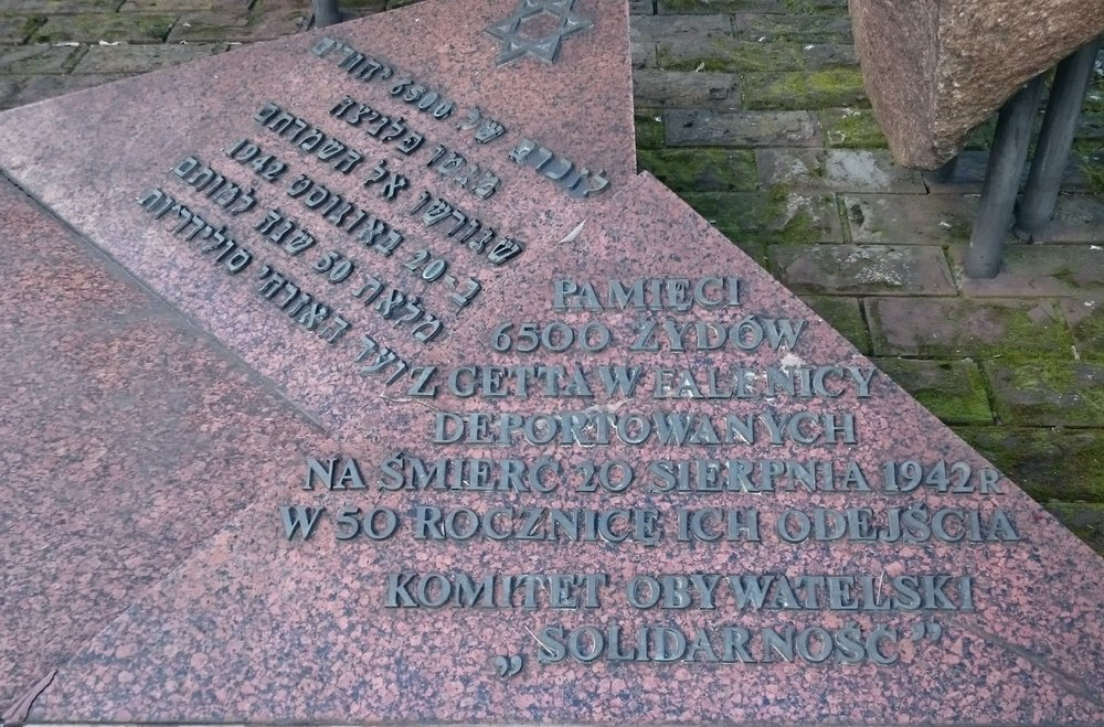 "You can see it in Hebrew and Polish.  Exact translation into English: Memorial of the 6500 Jews from the ghetto in Falenica (a region of Warsaw) who were deported to death on 20 August, 1942. At the 50th anniversary of their leaving. Put up by the civic committee ""Solidarity""."