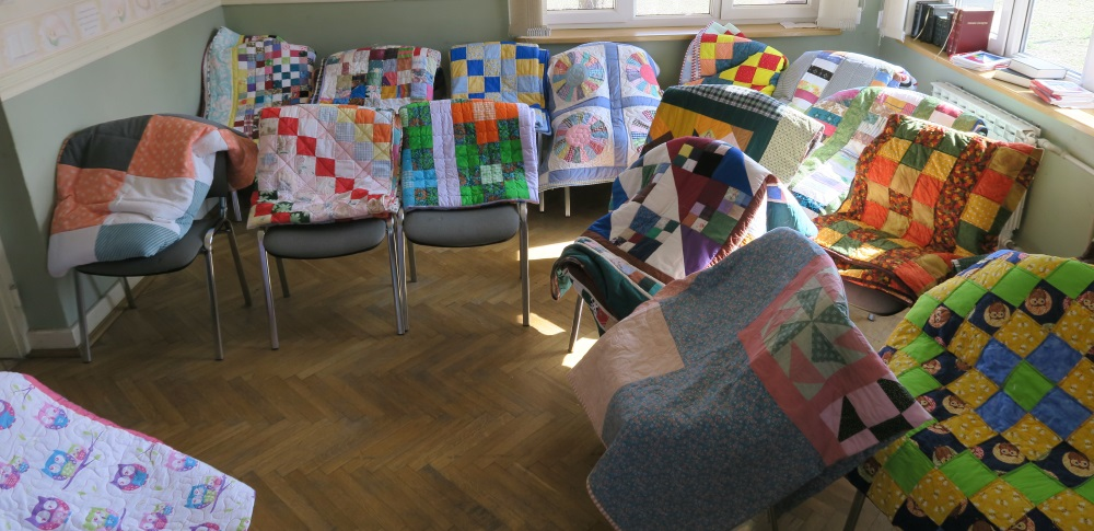 I draped quilts over chairs and had about 60 out at time for people to choose from.  When some were taken, I'd replace them with others in order to keep a good selection available. People would walk through and choose what appealed to them.