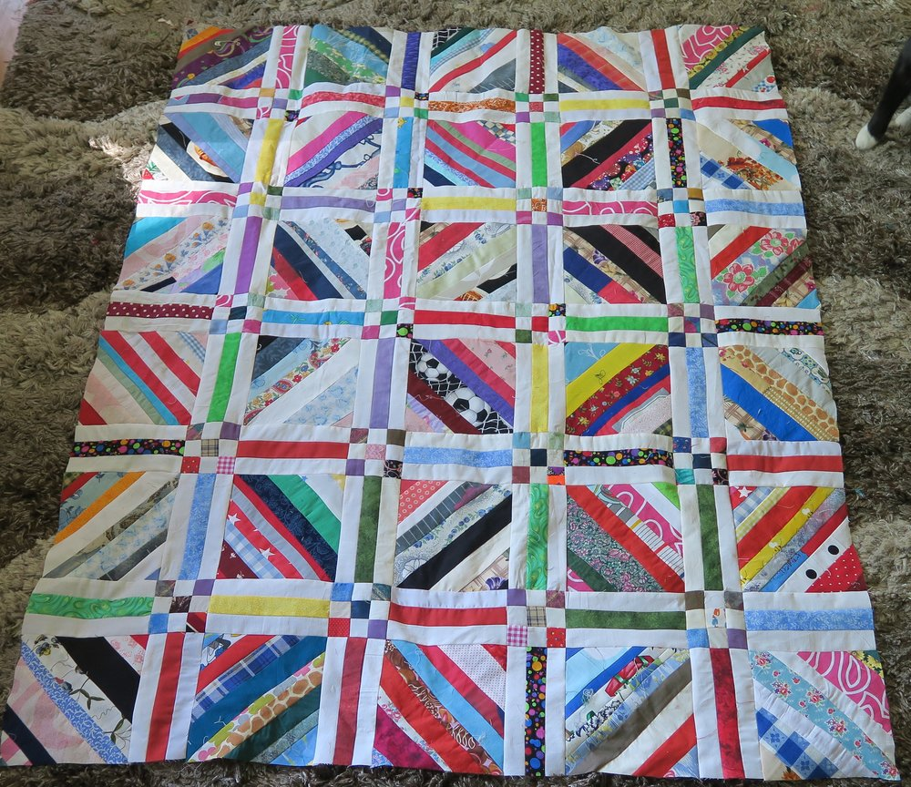 "It is now about 42""x52"" and a nice baby quilt size. :)  But that's NOT the size I want to make.  I have 50 of the 6.5"" blocks made and I figure I need 100. There are only 30 of them in this top as of this picture. I'll need to make some more 9 patches and sashing pieces."