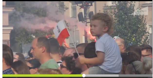 Here a child is sitting on his dad's shoulders while some are setting off flares and sirens are going off in Warsaw.  Everyone stands at attention for a minutes. This is from 2017 - this year.
