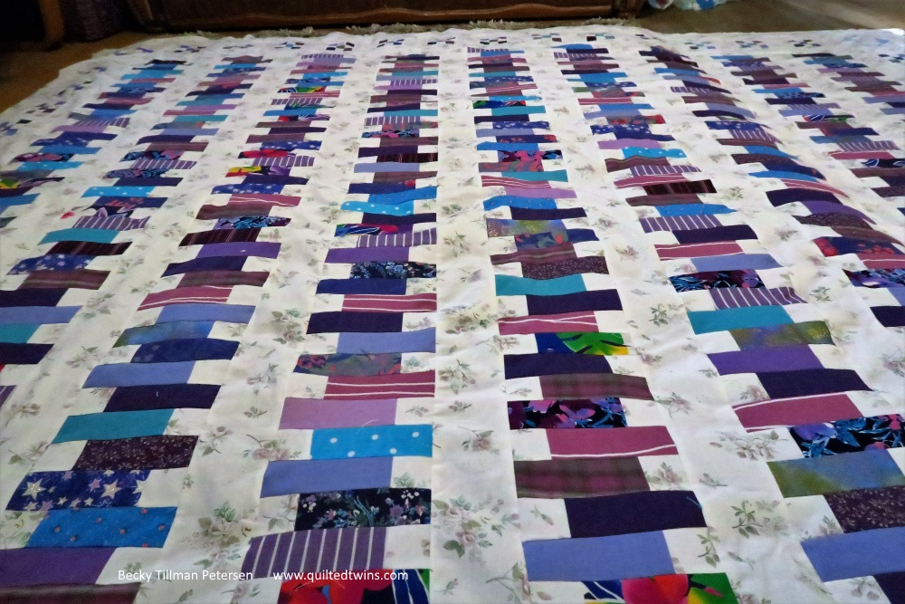 Picture of lbrary stacks quilt quilt with purple and blue strips on white backgroundd