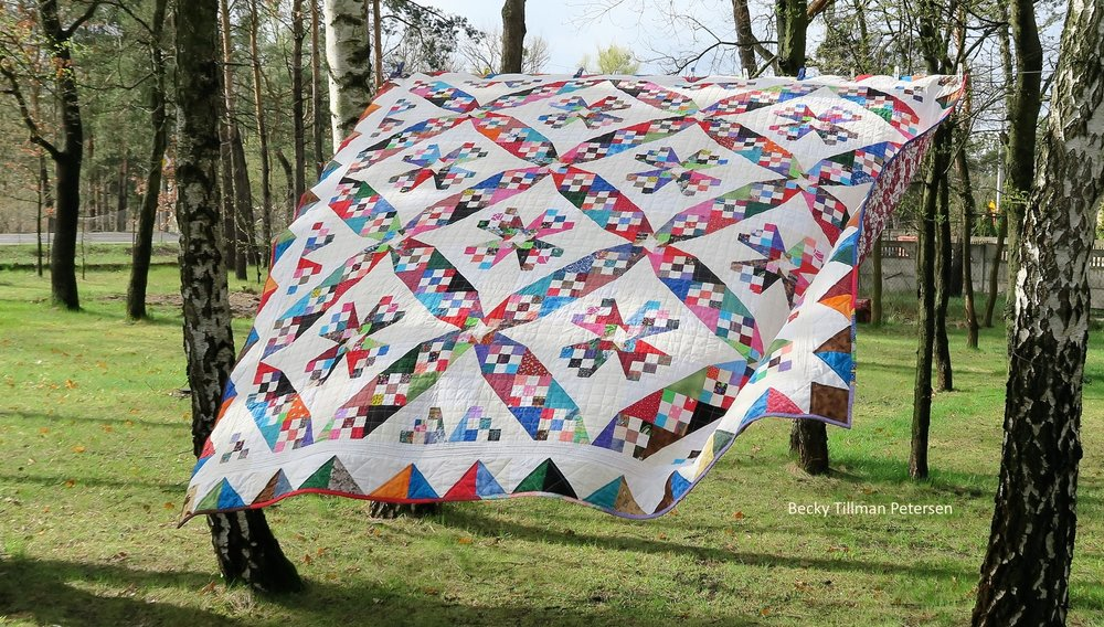 picture of  blades of color quilt, colorful windmill blades on a quilt with a white background