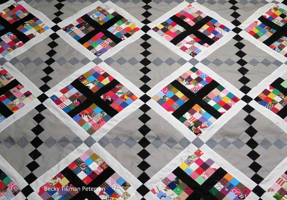 Picture of classy scraps quilt, square scrap conneted to white and black rectangles with gray background