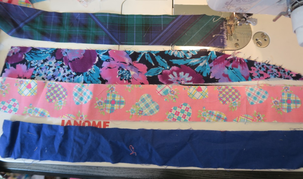 picture of two inch strips of fabric used in tutorial on quilting: a green and blue striped two inch strip, blue and pink floral two inch strip of fabric, pink with heart two inch strip of fabric, and a solid blue two inch strip of fabric. All on a sewing machine
