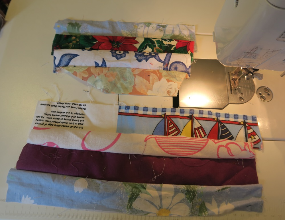 picture of two inch fabric sewn together on top of sewing machine: 7 different pieces of two inch fabric ranging from solid burgandy to dark blue floral-like patterns