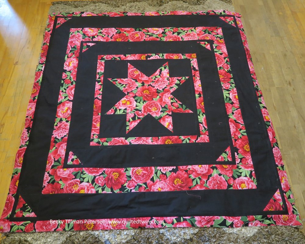 I put those half square triangles in the corners - made it seem like mounting corners for scrapbooking or old timey photo albums. I also floated the inside star by putting another strip of black between the star points and the floral border around it.