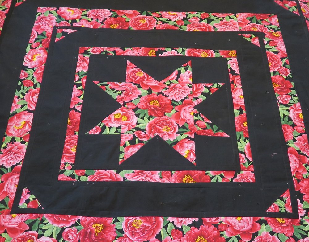 close up picture of quilt with star and pink roses revealing rose trangles at the corners black background is more pronounced in this photo