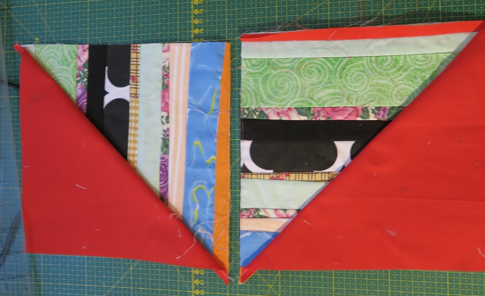 Cut red triangular, half squares sewn to scrap triangular block