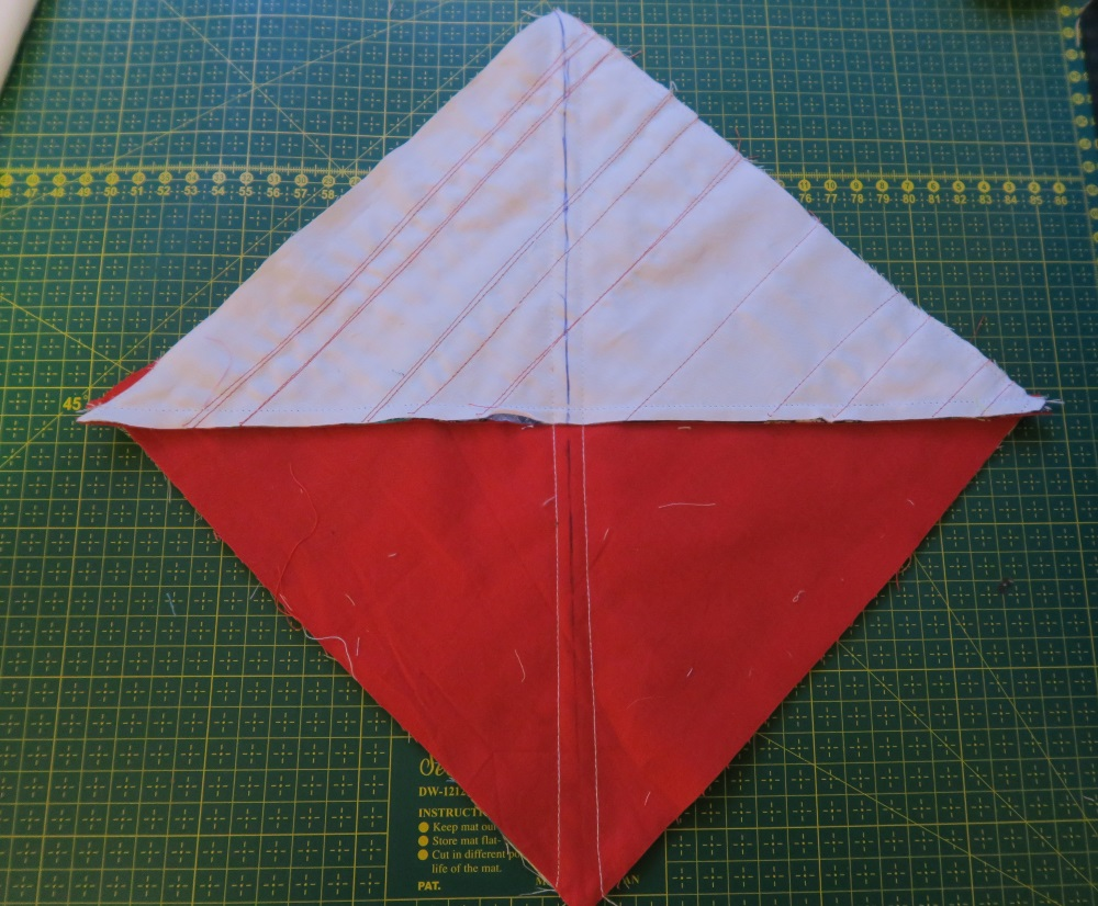 Square red block with half square triangle white block with lines drawn across on top of half of red block, all sitting on top of green quilting cutting board
