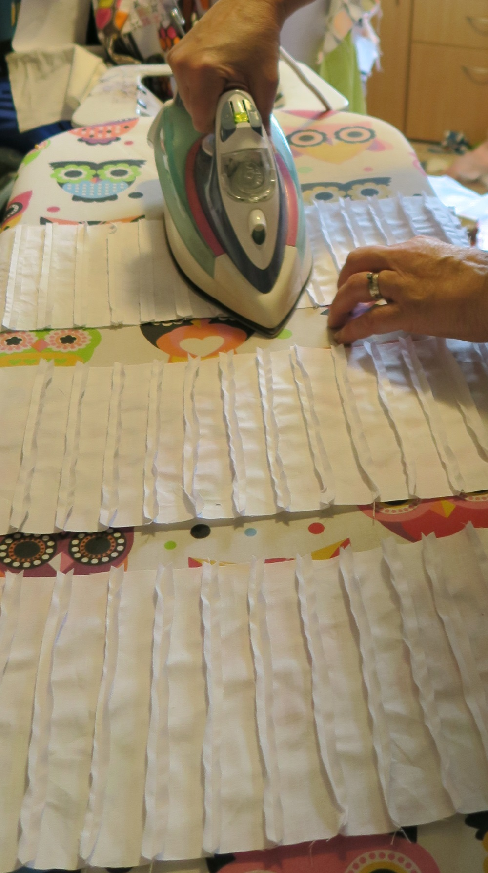 Rachael pressing open border. Previously sewn white fabric is being pressed on a whit ironing board with an iron. Three different sheets of white sewn fabric is visiable.