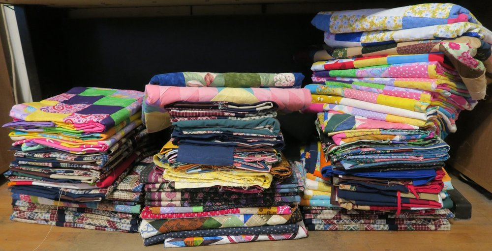 There are 72 tops here.  From the left in the stacks, there are 20, 22, and 30.  I have more I am trying to finish up today - but they need another round of borders and a last pressing.
