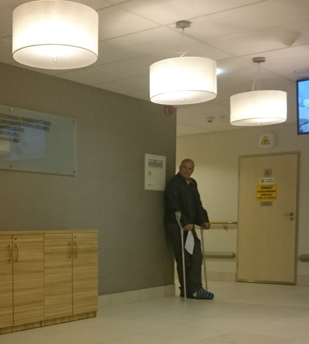 "Mike is standing here waiting for the lady who does the x rays. He's holding a paper giving the ""order"" for the x rays."