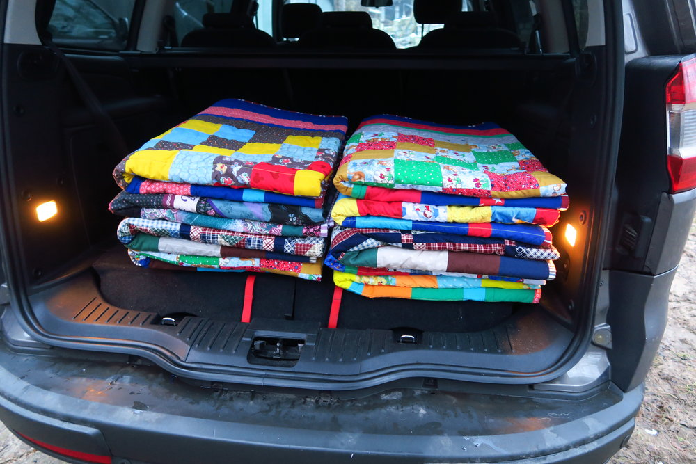 Quilts in the back of the vehicle ready to head to the church building where I am keeping them til I have a give-away.
