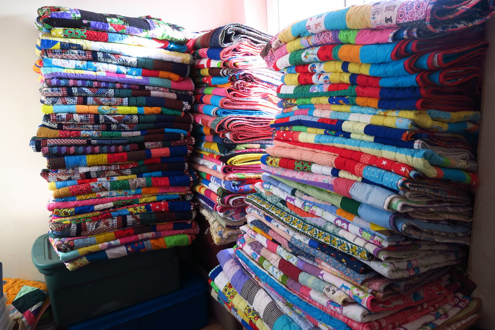 These piles have 50 quilts that have been recently added. Since I do have 70 more to put here as well, no doubt I will start a fourth pile in order to keep them all from falling over on to the floor. I have another plastic trunk I can put right next to the pile on the right so they won't start out on the floor. I will the stack them up from the trunk.