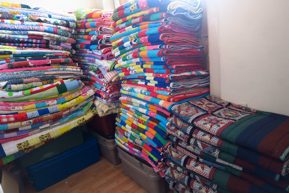 This is after I've added this group of quilts to these stacks.  The men's quilts are in the front here on the right, the ladies/more adult looking quilts straight ahead on the left and the kids' quilts are in front of the window. by far the majority of what I have.