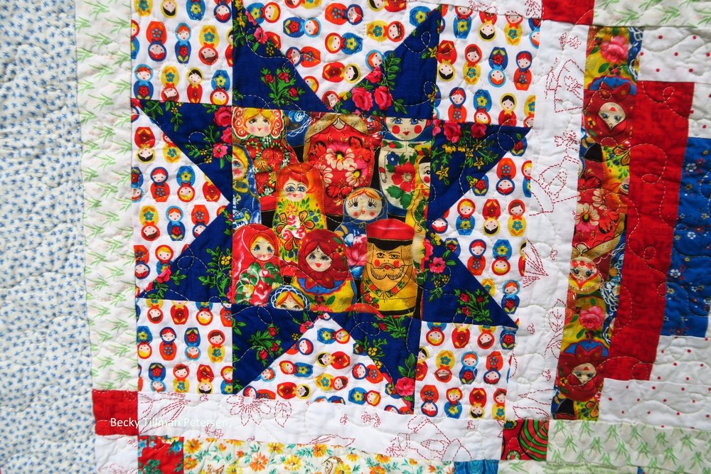 This background fabric is the  Russian stacking dolls  that my sis has - only $4.99/yard!. The blue floral is a Polilsh fabric purchased locally and the center fabric - stacking dolls I bought on Ebay - it was pricey, but perfect for this quilt!