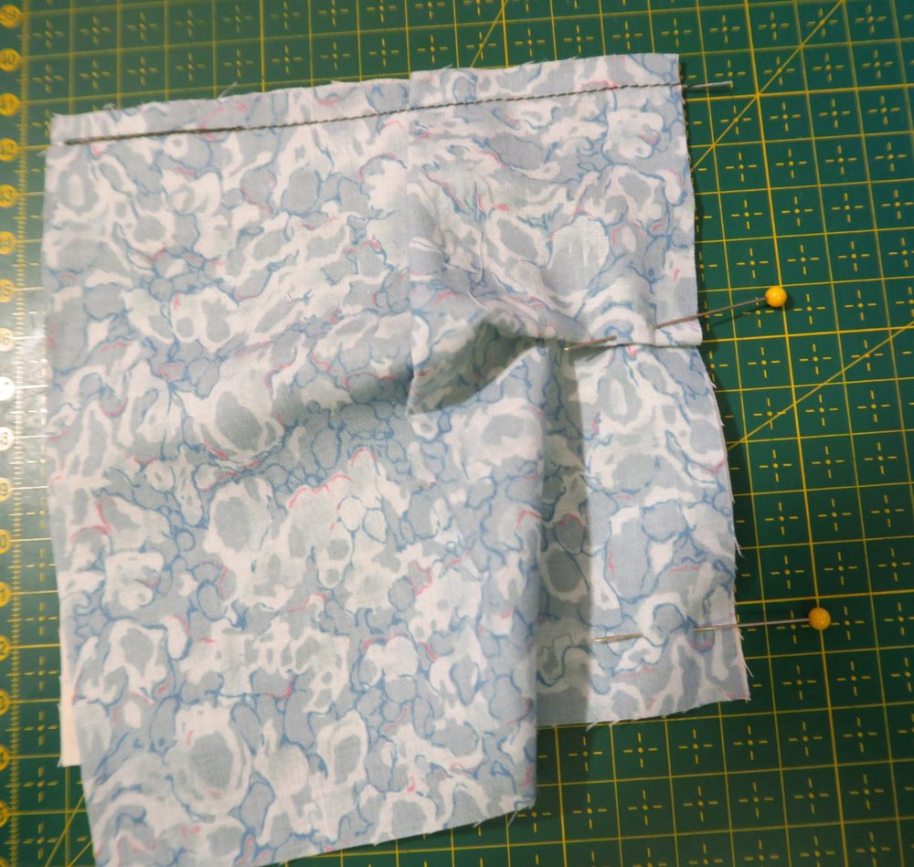 """Pin the next side, folding a pleat into the fabric so that the 6"""" blue fabric fits to the same size as the  5"""" white backing."""