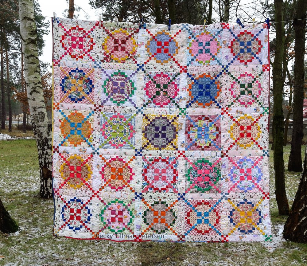 """Design - classic Burgoyne Surrounded block  Inspired by - wanting to make a light and airy one as I had made a couple of this pattern before in a civil war look - tans, browns, dark reds, etc. I opted for pretty, fun, light-hearted. I checked out several blogs. I made it as a quilt along in a Facebook group I am in.  Regrets - This 100% upcycled quilt has a few spots where I could have been more careful choosing the fabrics. I noticed while quilting, for example, that one or two of the pieces had a buttonhole slit in it. I don't know why I didn't notice that while piecing. I had to quilt over the buttonhole and make sure that it was no more! Normally I didn't keep the section of blouses where the buttonholes were but we had bought some second hand fabrics from a lady back in 2015 and she """"very carefully"""" took all the blouses apart and ironed everything! I generally don't keep that section of the shirt and definitely don't bother to work with that kind of finesse when de-constructing a shirt."""