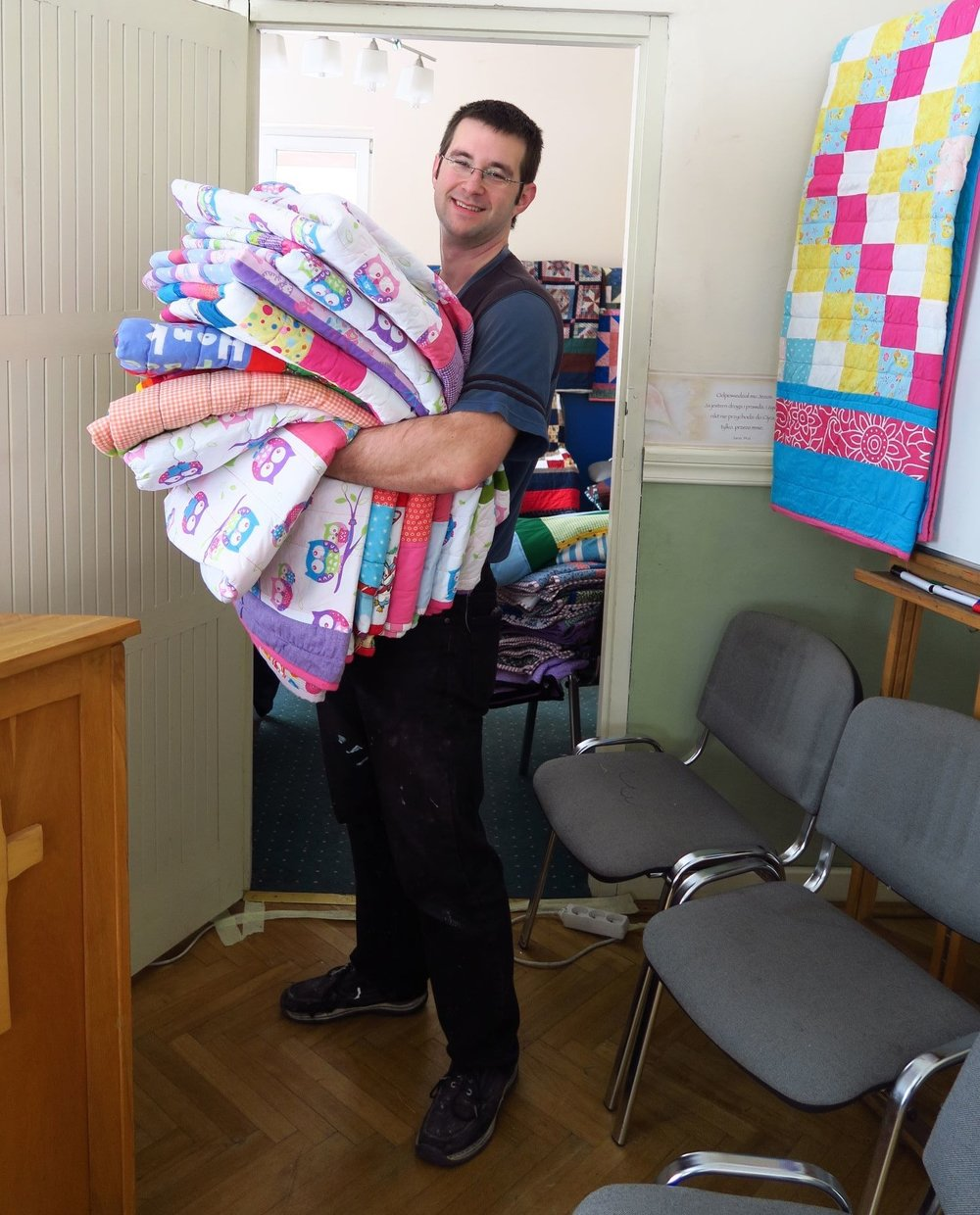 Tim carrying a load of quilts.