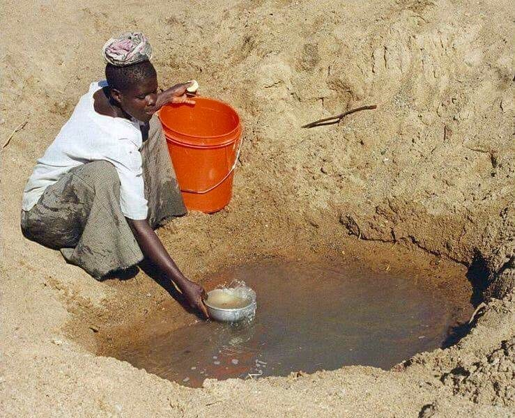 young girl picking up water from dirty borehole