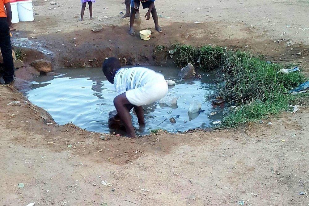 kid collecting water, Zimbabwe.