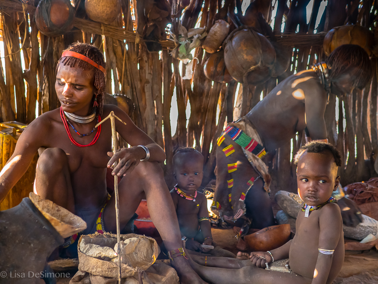 Hamar Tribe women grinding sorghum and making coffee