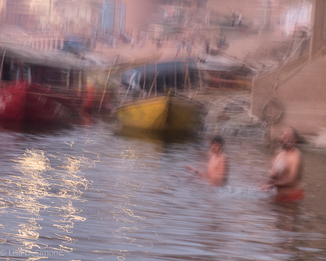 A father and son taking an early morning bath in the Ganges River in Varanasi, India.