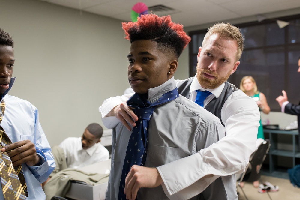 Coach Kyle Bennison of Memphis Athletic Ministries assist a recipient with his tie.