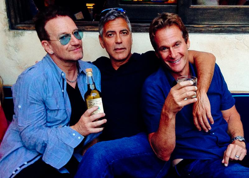 """Yep, das Foto ist ein bisschen unscharf – aber so ganz klar sind die drei Herren auch nicht mehr: Bono, George Clooney und Rande Gerber trinken aufs beste Mannesalter im """"Cafe Habana"""" – wo Malibu noch idyllisch, Kuba noch exotisch und Tequila ein echtes Lebensmittel ist. Prost!"""