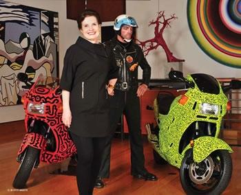 """Billie Milam Weisman, heute Managerin der Art Foundation, mit einem """"Rocker"""" von Duane Hanson und zwei Motorrädern, die Keith Haring gestaltet hat. Links ein Lichtenstein: Wir befinden uns im Anbau zur Villa, der 1991 Raum schuf für die Riesenformate"""