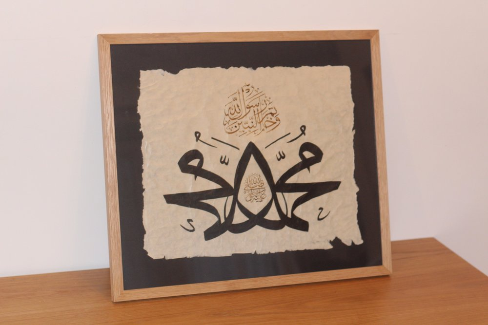 The name of Prophet Muhammad (pbuh) written in Muthanna style (mirror images); script: Thuluth