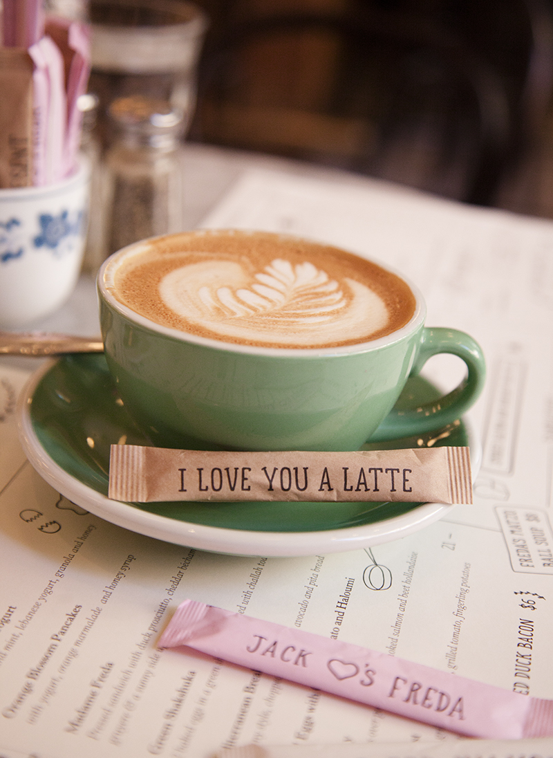 A cappuccino suited in an  Acme  cup and saucer set, alongside Jack's Wife Freda custom-illustrated sugar packets.
