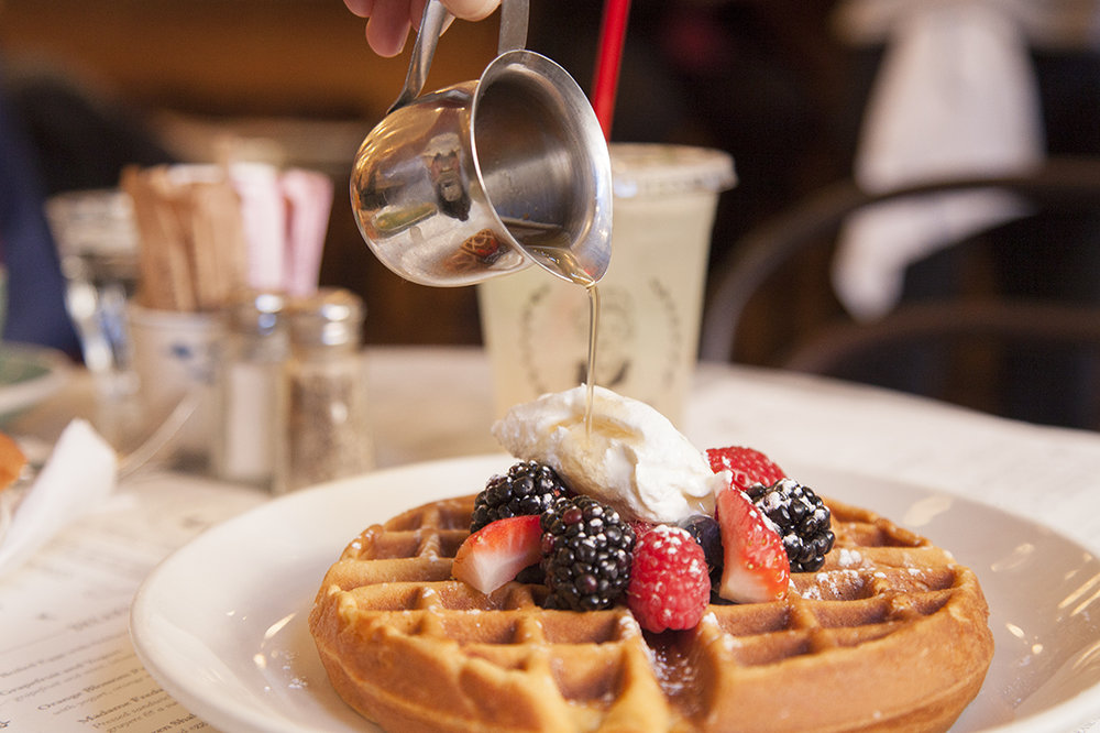 The rosewater waffle topped with mixed berries and Lebanese yogurt, served with a  mini bell pitcher  of honey syrup.