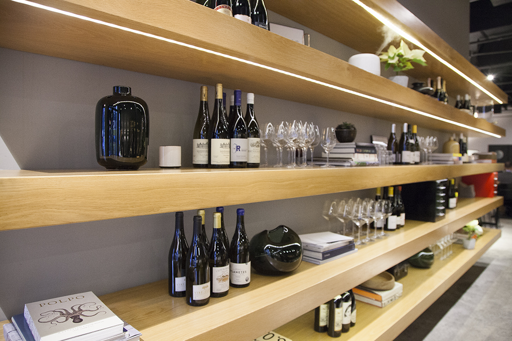 Wooden shelves line the walls of Cosme, filled with modern glassware, wine bottles and cookbooks.