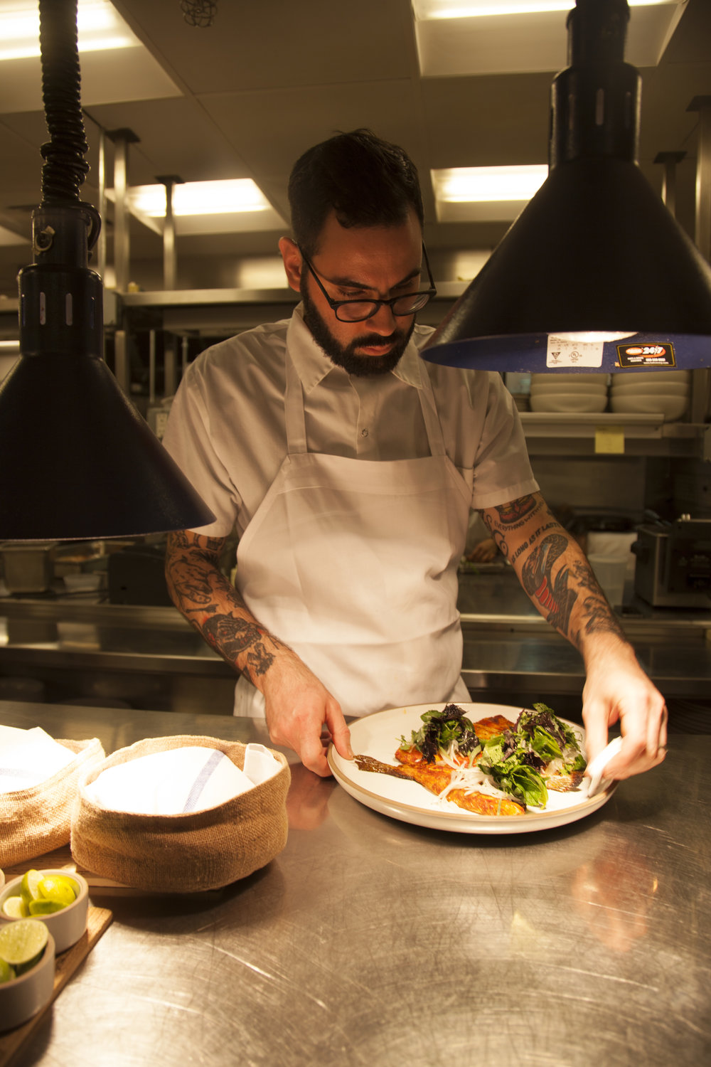 Sous chef   Luis Herrera   adds finishing touches to a plate of branzino   a la talla.