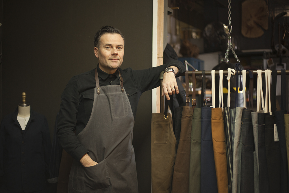 Iestyn wears the  Bond Street Apron  in grey waxed canvas.